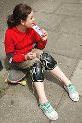 Teenage girl having a drink whilst sitting on her skateboard.