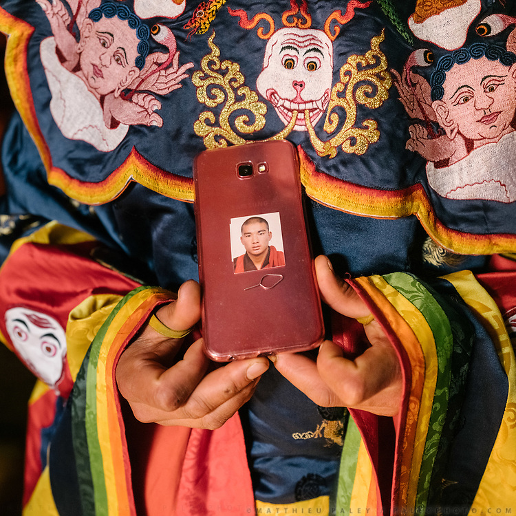 Monk shows his phone. The Tshechu of the Gasa monastery on the road leading to Laya. Tshechu are annual religious Bhutanese festivals held in each district on the tenth day of a month of the lunar Tibetan calendar. Tshechus are large social gatherings, which perform the function of social bonding among people of remote and spread-out villages.