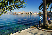 Korcula old town, viewed from the West, with two children (9 years old, 5 years old) walking along waterside in foreground. Korcula old town, island of Korcula, Croatia