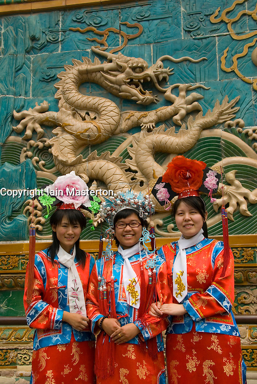 Girls in traditional costume pose in front of famous Nine Dragon Screen Wall in Beihai Park Beijing