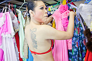 """Oct. 7, 2009 -- BANGKOK, THAILAND:  A """"ladyboy"""" selects her outfit performing at the Mambo Cabaret in Bangkok, Thailand. The performers at the Mambo Cabaret in Bangkok, Thailand are all """"Ladyboys,"""" or kathoeys in Thai. Recognized as a third gender, between male and female, they are born biologically male but live their lives as women. Many kathoey realize they are third gender in their early teens, some only as old 12 or 13. Kathoeys frequently undergo gender reassignment surgery to become women. Being a kathoey in Thailand does not carry the same negative connotation that being a transgendered person in the West does. A number of prominent Thai entertainers are kathoeys. Photo by Jack Kurtz / ZUMA Press"""