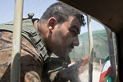 © Licensed to London News Pictures. 30/06/2014. Khanaqin, UK Khanaqin, Iraq. A Kurdish peshmerga fighter peers to see the road ahead from the back of a peshmerga pick up truck in Jalawla, Iraq. Counted by Kurds as part of their homeland, fighting in the town of Jalawla now consists of occasional skirmishes and exchanges of fire between snipers and heavy machine guns on both sides.<br />   The peshmerga, roughly translated as those who fight, is at present engaged in fighting ISIS all along the borders of the relatively safe semi-automatous province of Iraqi-Kurdistan. Though a well organised and experienced fighting force they are currently facing ISIS insurgents armed with superior armament taken from the Iraqi Army after they retreated on several fronts. Photo credit : Matt Cetti-Roberts/LNP
