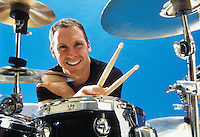 Portrait of a early 30's Caucasian man smiling while leaning on his drum set holding his drum sticks.<br />