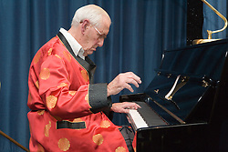 Elderly man playing grand piano,
