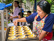 "07 APRIL 2013 - CHIANG MAI, CHIANG MAI, THAILAND:  A vendor makes ""Khanom Bueang"" or crispy coconut pancakes with coconut cream filling, a popular Thai desert and snack, at Chiang Mai's ""Walking Street."" The Walking Street Market starts at Thapae Gate and runs along the length of Ratchadamnoen Road through the heart of the Old City and has become a Chiang Mai institution. Chiang Mai is the largest town in northern Thailand and is popular with tourists and backpackers.       PHOTO BY JACK KURTZ"