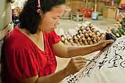 25 JUNE 2011 - CHIANG MAI, THAILAND: A woman paints an umbrella in a craft village near Chiang Mai Thailand. Umbrellas from the Chiang Mai are prized throughout Thailand for the quality of workmanship. They were once used almost exclusively as sun parasols by Buddhist monks and royalty but now are used by hotels, restaurants and collectors.   PHOTO BY JACK KURTZ