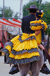 "Europe, Spain, Andalucia, Sevilla, man and woman in flamenco dress riding horse during ""Feria de Abril"" festival, held annually in April"