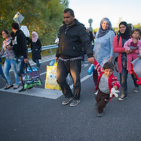 Illegal migrants walk to a refugee camp for administration after they tried to break out and run away from custody through a line of police officers near Roszke (about 174 km South of capital city Budapest), Hungary on September 07, 2015. ATTILA VOLGYI