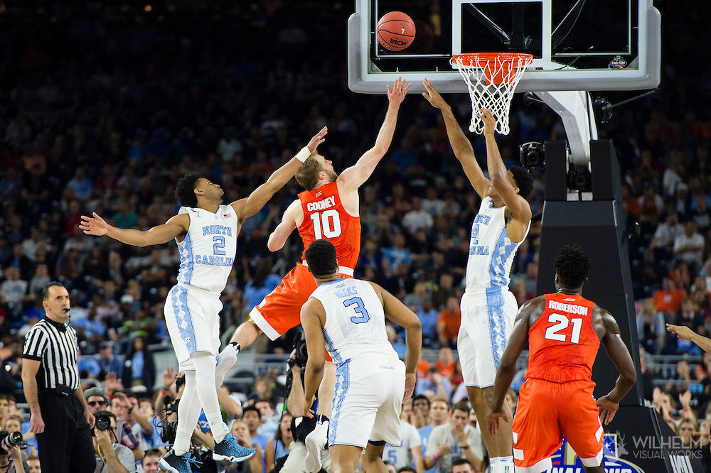 02 APR 2016: Guard Trevor Cooney (10) of Syracuse University shoots between Guard Joel Berry III (2) of the University of North Carolina and Forward Isiah Hicks (4) of the University of North Carolina during the 2016 NCAA Men's Division I Basketball Final Four Semifinal game held at NRG Stadium in Houston, TX. North Carolina defeated Syracuse 83-66 to advance to the championship game.  Brett Wilhelm/NCAA Photos