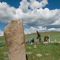 A Smithsonian Museum archaeology team studies a 2700+ year-old,  khirigsur burial mound at a site near Lake Erkhel & Muren, Mongolia.  An ancient Deer Stone stands in the foreground (from the same era).