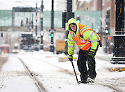 UTA employee Chris McFadden clears snow from the southbound rail track between 100 and 200 South in Downtown Salt Lake City as snow continues to fall, Friday, Dec. 28, 2012.