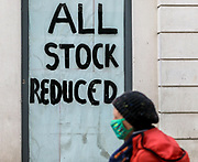 23rd February, Cheltenham, England. A shopper walks past an 'ALL STOCK REDUCED SIGN' in the Cheltenham Town centre during the 3rd national lockdown.