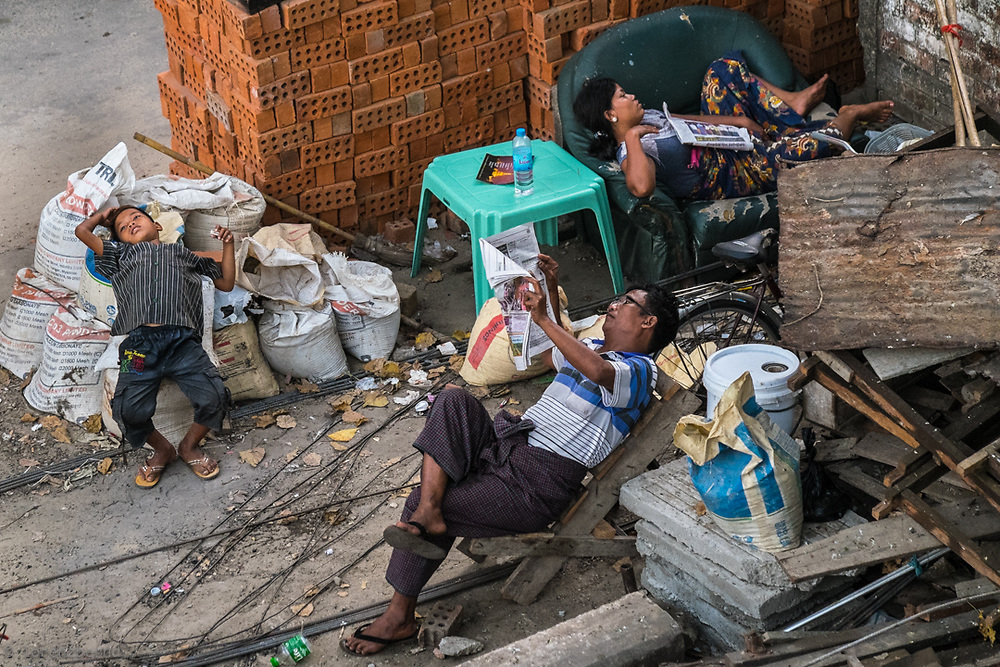 Resting in Chaos. Thanks to a nearby bridge i was able to isolate this family relaxing in the street of Yangon, Myanmar.<br /> Photo by Lorenz Berna