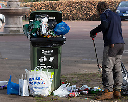 © Licensed to London News Pictures. 31/03/2021. London, UK. A worker picks up rubbish in Greenwich Park after hundreds of people visited the park to enjoy sunny weather and take advantage of new lockdown rules that allow groups of six to meet outside. Photo credit: George Cracknell Wright/LNP