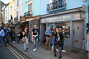 People outside the Portobello Road Antigues Gallery in Notting Hill, West London, England, United Kingdom. People enjoying a sunny day out hanging out at the famous Sunday market, when the antique stalls line the street.  Portobello Market is the worlds largest antiques market with over 1,000 dealers selling every kind of antique and collectible. Visitors flock from all over the world to walk along one of Londons best loved streets.