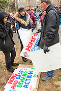 Marchers choose signs prior to the march across the Brooklyn Bridge. The March was sponsored by One Million Moms for Gun Control.
