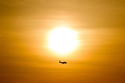 A Lockheed C130 Hercules transport aircraft in silhouette flies passed the setting sun in Yamato, Kanagawa, Japan. Tuesday may 1st 2018