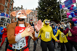 © Licensed to London News Pictures. 07/12/2019. LONDON, UK.  7 December 2019.  Participants take part in a warm up ahead of The 39th Great Christmas Pudding Race in Covent Garden, raising funds for Cancer Research as well as having lots of festive fun.  Photo credit: Stephen Chung/LNP