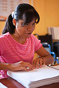 Nhem, a blind girl is proof reading a Braille schoolbook at the Krousar Thmey School for Deaf and Blind children in Phnom Penh. The Krousar Thmey Foundation assists underprivileged children across Cambodia.