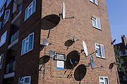 Satellite dishes on the side of a block of flats in a south London estate.