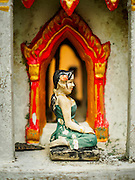 20 JULY 2015 - NONTHABURI, NONTHABURI, THAILAND:  A porcelain figure in spirit house in a neighborhood on the Chao Phraya River. This is in a neighborhood that is scheduled to be redeveloped and the people who live here might be evicted. The Chao Phraya promenade is development project of parks, walkways and recreational areas on the Chao Phraya River between Pin Klao and Phra Nang Klao Bridges. The 14 kilometer long promenade will cost approximately 14 billion Baht (407 million US Dollars). The project involves the forced eviction of more than 200 communities of people who live along the river, a dozen riverfront  temples, several schools, and privately-owned piers on both sides of the Chao Phraya River. Construction is scheduled on the project is scheduled to start in early 2016. There has been very little public input on the planned redevelopment.          PHOTO BY JACK KURTZ