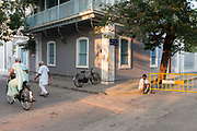 A man sits in the road waiting for work as a woman and a man exercise shortly after dawn. Pondicherry, India<br /> Pondicherry now Puducherry is a Union Territory of India and was a French territory until 1954 legally on 16 August 1962. The French Quarter of the town retains a strong French influence in terms of architecture and culture.