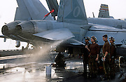 Brown-shirted plane captains, responsible for cleanliness and operating readiness of aircraft on deck, wash an F/A-18..On the deck of USS Harry S Truman, the largest and newest of the US Navy's fleet of new generation carriers, a 97,000 ton floating city with a crew of 5,137, 650 are women.
