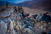 Marine Captain Ryan Maloney and a group of Afghan National Army soldiers rest at a bivouac site on top of a mountain ridge. Captain Maloney led a team of four Marines and a company of Afghan soldiers on an overnight mission that resulted in one Taliban death and one civilian death.