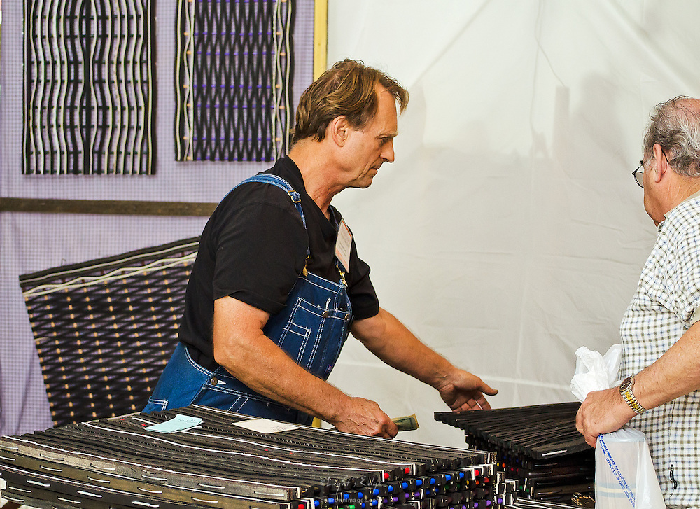 A regular vendor to the Wheaton Arts Fine Craft Fair handles a purchase of one of his hand made door mats made from recycled tires.