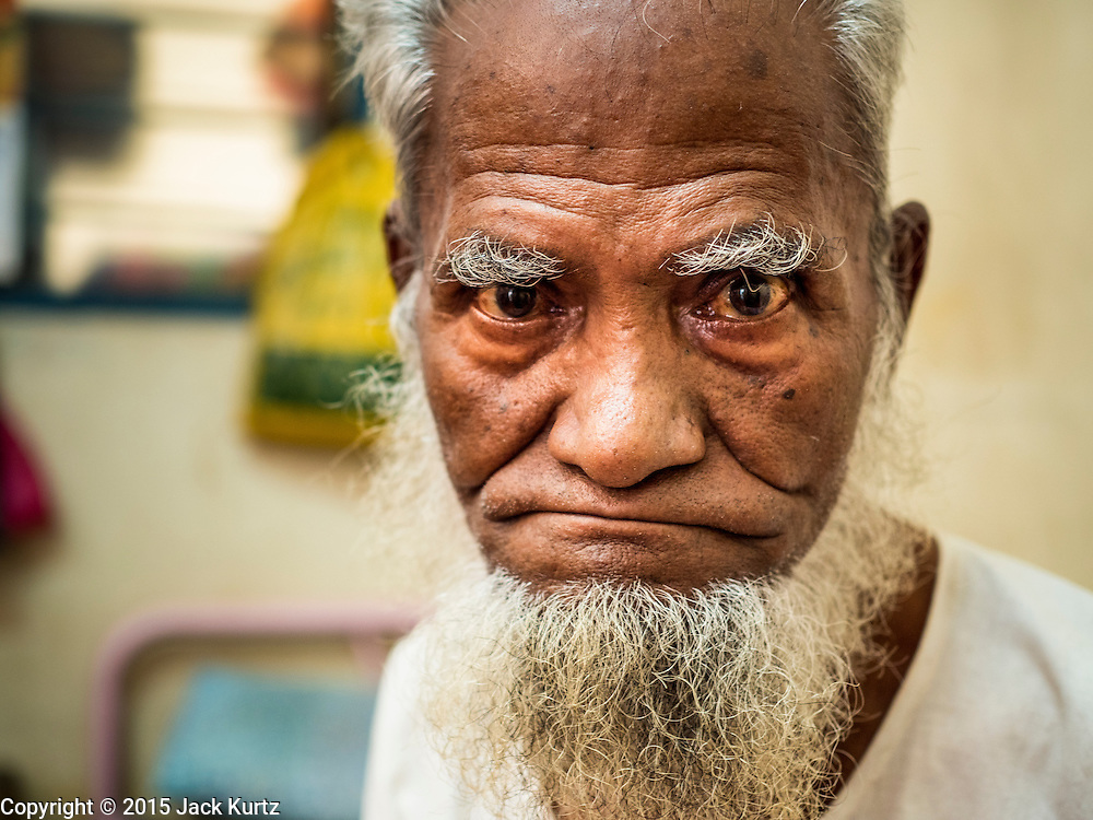 02 JUNE 2015 - KULAI, JOHORE, MALAYSIA: FOZOL AHMAD BIN HABI, a Rohingya refugee from Sittwe, Myanmar, in his home in Kulai, Malaysia. He was an Imam in Myanmar but now is not healthy enough to work or preach and relies on the kindness of his neighbors to meet his needs. He lives in a small room in a tenement he shares with seven other Rohingya families. The UN says the Rohingya, a Muslim minority in western Myanmar, are the most persecuted ethnic minority in the world. The government of Myanmar insists the Rohingya are illegal immigrants from Bangladesh and has refused to grant them citizenship. Most of the Rohingya in Myanmar have been confined to Internal Displaced Persons camp in Rakhine state, bordering Bangladesh. Thousands of Rohingya have fled Myanmar and settled in Malaysia. Most fled on small fishing trawlers. There are about 1,500 Rohingya in the town of Kulai, in the Malaysian state of Johore. Only about 500 of them have been granted official refugee status by the UN High Commissioner for Refugees. The rest live under the radar, relying on gifts from their community and taking menial jobs to make ends meet. They face harassment from Malaysian police who, the Rohingya say, extort bribes from them.     PHOTO BY JACK KURTZ