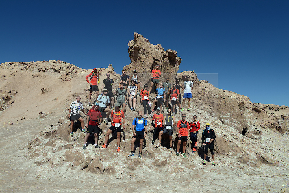 © Licensed to London News Pictures. 14/11/2013.<br /> <br /> The runners pose for a team group.<br /> <br /> Inaugural Volcano Marathon, Atacama Desert, Chile. The race took place in the Atacama Desert in Chile, beginning at an altitude of 4,400 metres (14,500 feet) in the vicinity of Lascar Volcano. It was a gruelling affair for many of the competitors who had to encounter some challenging hills and manage the impact of the heat and oxygen deprivation. The average altitude of the entire race was close to 4,000 metres and temperatures reached the mid 20s Celsius, or almost 80 Degrees Farenheit.<br /> <br /> Photo credit : Mike King/LNP<br /> <br /> Further information and link to video here: https://www.dropbox.com/s/0277bepxvo0t8il/Marathon%20copy.txt
