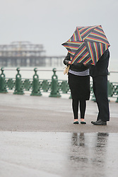 © under license to London News Pictures. 12/06/12. Heavy rainfall across the south east, three people walk along brighton seafront in the rain. The met office has issued severe weather warnings in England and Wales. Unseasonal weather in the south east has caused flooding across Sussex has been badly hit. Brighton XAVIER ITTER/LNP