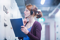 Young female engineer wearing headset and controlling a switch gear in control room, Freiburg im Breisgau, Baden-Wuerttemberg, Germany