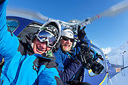 Tony Harrington and Arden Oskenan hanging out of the helicopter at Points North Heliskiing in Corova Alaska. MR