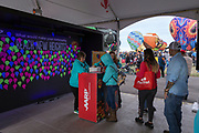 People line up to write notes for the commitment wall at the AARP Block Party at the Albuquerque International Balloon Fiesta in Albuquerque New Mexico USA on Oct. 7th, 2018.