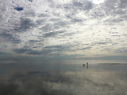 A man and his dog on a beach walk. The sky is creating a mirror image on the shore at low tide