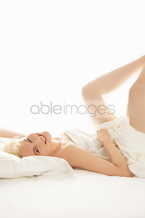 Young Woman Lying in Bed with Legs Raised