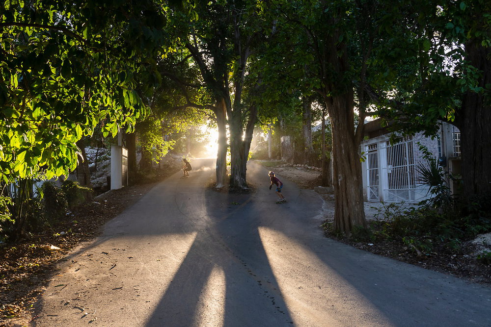 Bacalar, Mexico - June 3, 2021: Esahu Soto Rojas (left) and Oswaldo Romero (right) ride their skateboards down either side of a tree growing in the middle of a street in Bacalar.