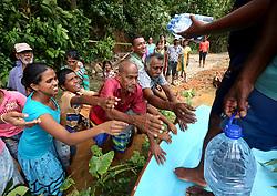 Sri Lankan flood victims receive drinkable water bottles by Sri Lankan Navy soldiers at Godagama, Matara, southern part of Sri Lanka on Tuesday 30 th May 2017. (Photo by Tharaka Basnayaka/NurPhoto) *** Please Use Credit from Credit Field ***