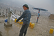 A boy fetches water from a water pump in Kabul, Afghanistan.