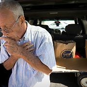 """San Bernardino resident Jim Hunter travels to 6 food banks per week for free food. Here, he leaves with his food provided by Second Chance Ministry. Hunter lives on his and his wife's social security and his hobbled with medical bills. He has exhaused his unemployment and his son recently moved back home. """"I'm very anti-religion,"""" Hunter explained after leaving with his food. """"But I need the extra food."""""""