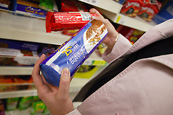 Woman checking fat content on a packet of biscuits,