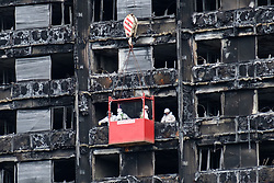 August 16, 2017 - London, London, UK - Workmen in a crane outside the Grenfell residential tower block in West London are seen wrapping the tower with a cling film type material. The tower was engulfed by a fire two months ago causing at least 80 deaths and over 70 injuries. Up to 200 survivors are still living in hotels and have resorted to searching for new homes themselves out of frustration at the council's rehousing efforts. (Credit Image: © Ray Tang via ZUMA Wire)