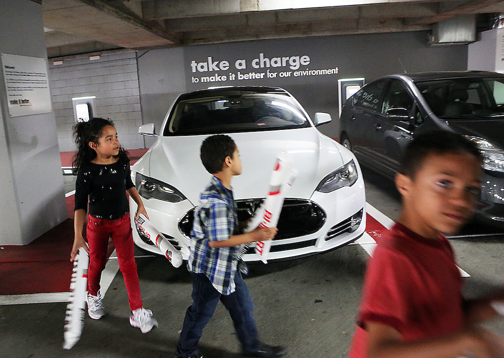 Anaya Dorsey, 6, Levi Dorsey, 5, and Josiah Dorsey, 8, walk from a friend's Tesla int the arena. Electric cars charge at the Moda Center arena while the Portland Trailblazers host the Golden State Warriors in an National Basketball Association game in Portland, Ore.