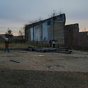As dusk falls over Baptist Town, children roam by an abandoned building, breaking old appliances and killing time, Greenwood, Mississippi, November 22, 2014.