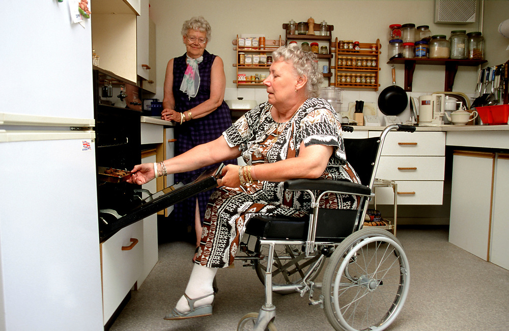 Disabled female using specially designed low level cooker in an adapted  wheelchair friendly kitchen,