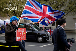 """© Licensed to London News Pictures. 05/03/2019. London, UK. An anti-Brexit protester sits outside Parliament with a """"Brexit: is it worth it?"""" placard. Secretary of State for Exiting the European Union Stephen Barclay and Attorney General Geoffrey Cox QC are in Brussels today to try and secure further legal assurances from the EU over the Irish backstop. Photo credit: Rob Pinney/LNP"""