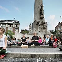 """Nederland, Amsterdam , 28 juli 2011..Meditatie op de Dam voor wereldvrede.. deelneem- .ster aan de 'MedMob', de .meditatie-variant van de .flashmob, ofwel verras- .singsactie. De MedMob .vond voor het eerst tege- .lijk plaats in 80 steden. In .Amsterdam slenteren toe- .risten gewoon door. Klin- .kenberg: """"Toch geloof ik .dat deze groep goede ener- .gie heeft overgebracht."""" ..Foto:Jean-Pierre Jans"""