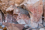 In Argentina, Cueva de las Manos (Spanish for Cave of Hands) displays some of the earliest known human art in the Americas. Located in a scenic canyon of the Pinturas River, Cave of Hands is reached by remote paved and steep gravel roads, 169 km (105 miles) south of the town of Perito Moreno, in Santa Cruz Province, Argentina, in the South American region of Patagonia. This striking artwork is honored on UNESCO's World Heritage List. Dating to around 5000 BCE, the silhouette paintings of mostly left hands were sprayed using a bone pipe held in the right hand. The age of the paintings was calculated from pigments found in layers of charcoal from human fires and bone remains of the spraying pipes. The hunting scenes (mostly guanaco) and representations of animals and human life all date older than the stenciled hands, to around 7300 BCE. A favorite hunting tool was the bola, where interconnected cords with weights on either end were thrown to trap animal legs. The site was last inhabited around 700 CE, possibly by ancestors of the Tehuelche people. Cueva de las Manos was first explored by researchers in 1949, followed by more extensive studies done in the 1960s. Varying paint colors come from different mineral pigments: iron oxides for red and purple, kaolin for white, natrojarosite for yellow, and manganese oxide for black.