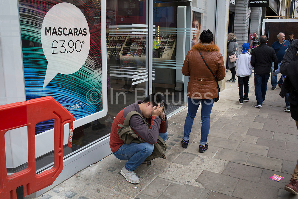 Man out shopping shows signs of despair holding his head in his hands outside a make up shop in London, England, United Kingdom.